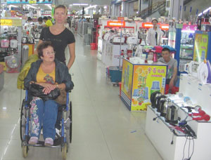 Фото. Хуньчунь (КНР). Православные добровольцы сопровождают инвалидов-спинальников в их поездке по Китаю: помогают передвигаться по торговому центру